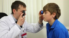 Ophthalmologist inspects  boy eye through lens and ophthalmoscope. - stock footage