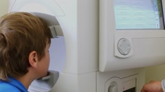 Boy checks  visual field at automatic perimeter. Stock Footage