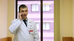 Doctor in white lab coat talks cell phone at room against window. Stock Footage