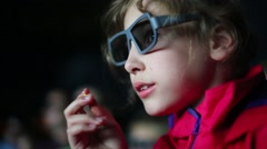 Little girl watch a movie in 3D glasses at the cinema. - stock footage