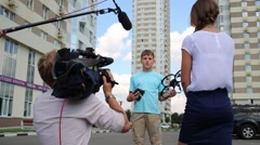 Boy operator of remote control answers questions of correspondent - stock footage