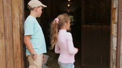 Boy and girl stand at stable gate looking inside it. Stock Footage