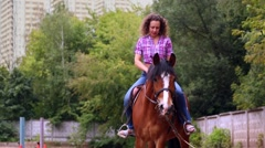 Young woman rides on bay horse under supervision of instructor Stock Footage