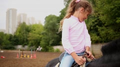 Little girl sits in saddle on dark horse at open area for dressage. Stock Footage