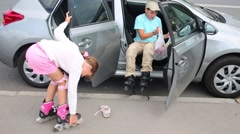 Boy and girl put on roller skates near the car before skating. Stock Footage