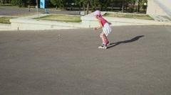 Little girl rides zigzag on roller skates down asphalt slope Stock Footage