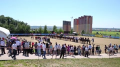 Spectators look at the riders lined up in the arena Stock Footage