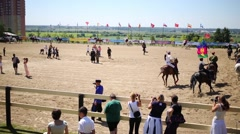Horsemen galloping around at the arena of equestrian sports complex Stock Footage