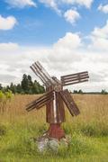antique wooden windmill in rye field - stock photo