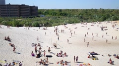 A crowd of people resting on the sandy beach and swim in water Stock Footage
