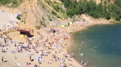 A crowd of people sunbathing and relaxing on the sandy beach Stock Footage