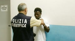 identification of africans migrats in Sicily by the italian police - stock footage