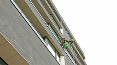 4k Workers washing the windows facade of a modern office building Stock Footage