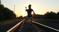 Silhouette of a dancing girl on railway in light of setting sun Stock Footage