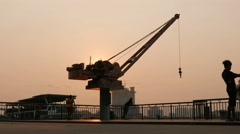 Old Henry J.Coles dock crane against dusk sky, people messing around, timelapse Stock Footage