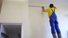 A worker measures the distance and makes a mark on the wall Stock Footage
