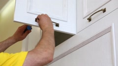A worker fastens the handle to the cabinet door using screwdriver Stock Footage