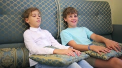 Boy and girl sits on a sofa with pillows on knees, the boy laughs Stock Footage