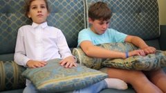 Boy and girl sits with a serious expression of faces and smile - stock footage