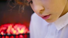 Lips of girl who reads a book next to the burning fireplace Stock Footage