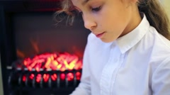 The girl sits next to a burning fireplace and reads a book Stock Footage