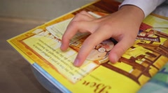 Hand of girl spends on the book by Gene Barretta while reading Stock Footage
