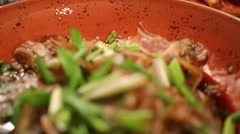 Fried pork ears with green onion on the plate in a restaurant Stock Footage