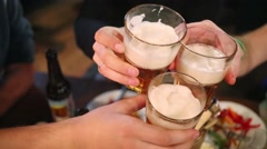 Stock Video Footage of Three people clink glasses of beer at the bar, visible only hand