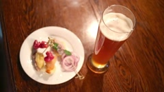 A glass with beer and snacks on a plate, male hand takes a glass Stock Footage