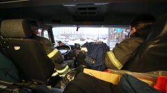 Two firefighters sits in fire truck and looks on the road Stock Footage