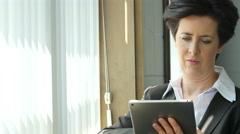Businesswoman using tablet/ipad in window light - stock footage