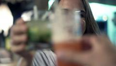 Beautiful woman raising toast with someone and drinking beverage in bar HD Stock Footage