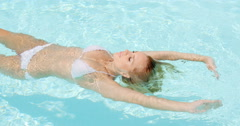 Sexy Young Woman Floating on Swimming Pool Stock Footage
