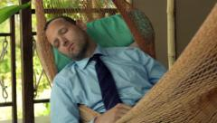 Young businessman sleeping on hammock on terrace Stock Footage