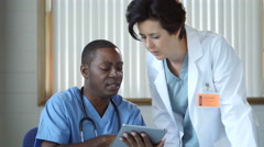 2 Doctors consulting in a medical office using an ipad/tablet - stock footage