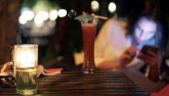 Woman drinking cocktail and using smartphone in trendy cafe at night Stock Footage