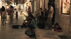 Young group play traditional greek music among people in shopping island street Stock Footage