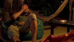 Young man talking on cellphone while lying on pouffe on terrace at night Stock Footage