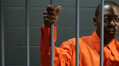 Black male inmate in jail cell, eyes down, dolly shot - stock footage