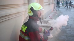 The man in the uniform of a fireman and helmet blows the smoke Stock Footage