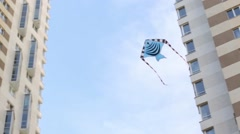 Blue striped kite flies in sky between the apartment buildings Stock Footage