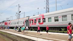 Passengers walk on the platform next to the train during a stop Stock Footage
