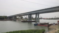 Bridge and a lot of construction cranes on the river bank Stock Footage