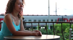 Woman (with model release) sits at the table at sunset Stock Footage