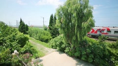 Garden and railroad tracks with a train with the acronym RZD Stock Footage