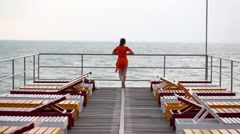 Girl stands and calls to come on pier with a row of sun loungers Stock Footage