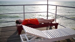 Woman lies on a deck chair on a pier against the sea Stock Footage