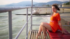 A woman sits on a sun lounger on a pier on the sea shore Stock Footage