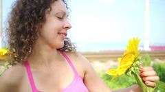 Smiling beautiful girl looks at the sunflower and camera Stock Footage