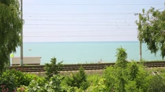 The train with the acronym RZD moves railroad tracks near the sea Stock Footage